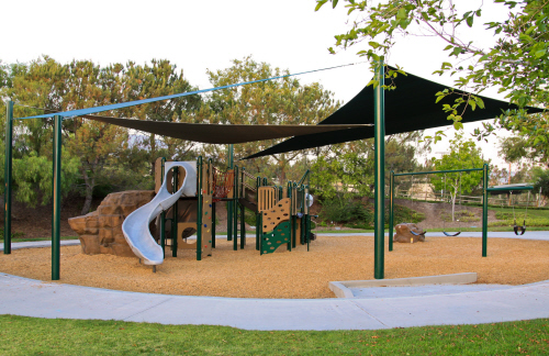 A shaded playground area in a city park